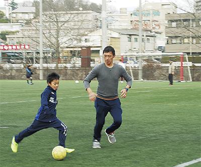人工芝でサッカーを楽しむ林さん親子