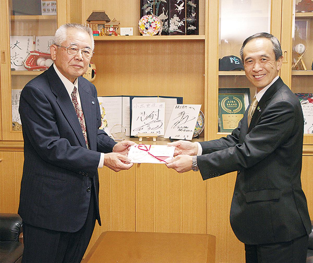 小出区長に寄付金を手渡す若林会長(左)