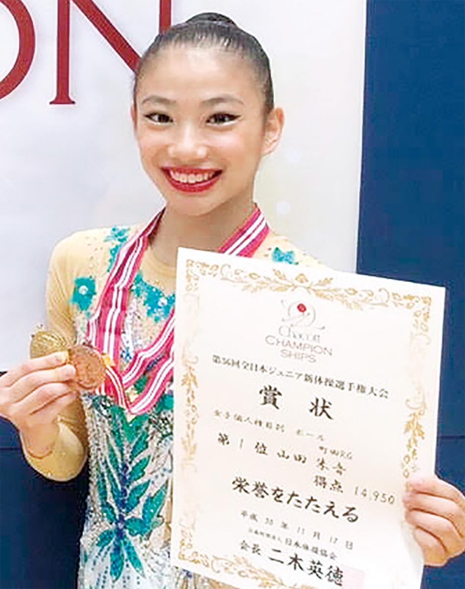 ボール種目1位の賞状とメダルを手にする山田さん