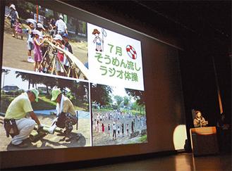 代表団体がスクリーンを使って一年の活動報告を行った