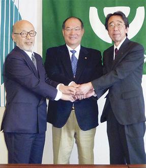 手をとりあう堀井理事長(左)、塚田会長(中央)、植田支社長
