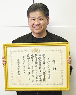 賞状を手に笑顔の吉川園長