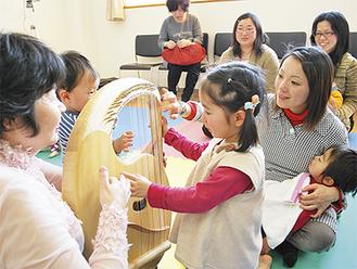 ライアーの弦を弾いて、聞こえてきた美しい音色に興味を示す子どもたち