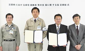 協定書を手にする鷲巣研二副区長(左から2人目)と山本八郎常務理事(右から2人目)