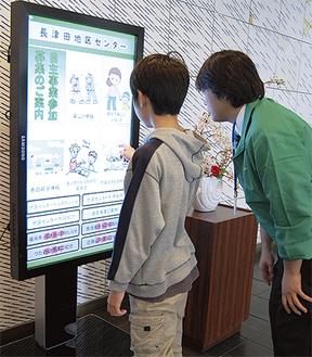 電子看板を使用する来場者(左)。パネルには長津田地区センターの情報が映し出されている。