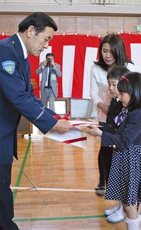 岩岡会長(左)からランドセルカバーを受け取る代表児童