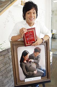 優秀賞の盾を手に取り笑顔を見せる中野さん。写真は今回の作品「もうすぐ会えるね。」