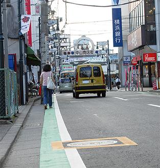 緑色のカラーベルト部分を通る歩行者