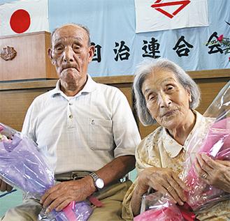 花束を手にする小野やゑ子さん(右)と池田久雄さん