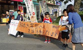 横断幕を掲げ募金を呼びかける児童