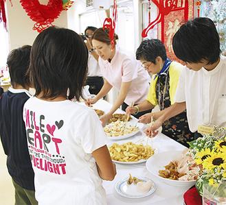 子どもたちに料理を取り分ける組合員ら