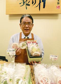 ミドリン・干支煎餅を手にとる加藤オーナー