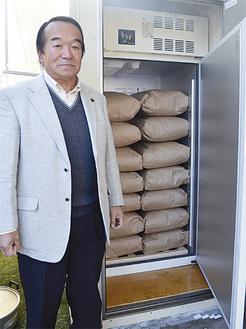 十日市場町自治会館の横に設置された専用冷蔵庫に入っている玄米。左は田中会長