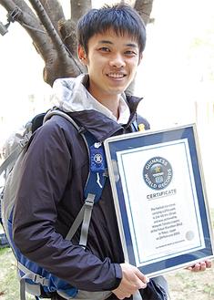 世界記録の認定書と、レースで使用したリュックサックを担ぐ高田さん