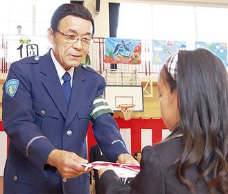 児童にカバーを手渡す岩岡会長