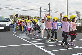 教習所コース内に設置された横断歩道を手をあげてわたる園児