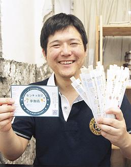 参加店のステッカーと割り箸を手にする伊藤さん