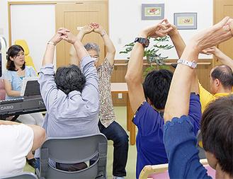 音楽に合わせて健康体操を行う参加者。写真左が廣瀬さん