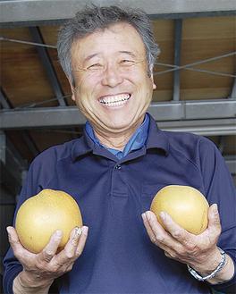 自慢の梨を手に喜ぶ菅沼さん