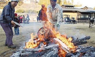 正月飾りを炎に投げ込む参加者