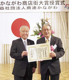 表彰状を手にする加藤龍昭理事長(右)と岡野誠一商連かながわ会長(左)