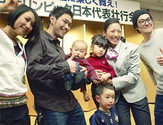 仲間から激励を受ける三星さん(右から2人目)。抱いているのは娘のすみれちゃん