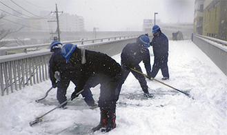 大雪のなか除雪にあたる作業員