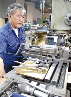 工場内で作業をする、長谷川社長
