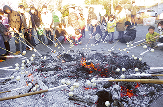 木棒につけた団子を火にかざす参加者