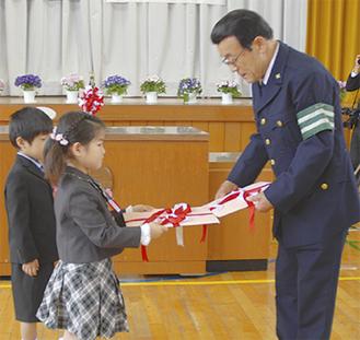 代表児童にカバーを手渡す岩岡会長