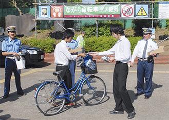 自転車通学者にチラシを渡す生徒たち