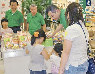 お菓子がもらえる抽選に参加する親子連れ