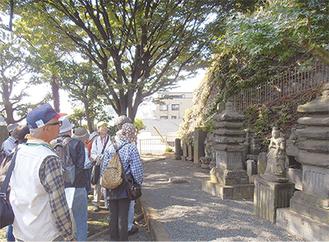 太郎父子の供養塔を眺める参加者ら