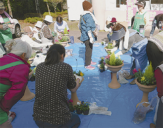 鉢に寄せ花を植える参加者