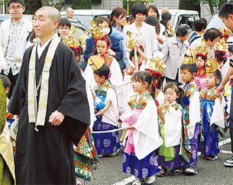色鮮やかな衣装に身を包んで行進する稚児ら(仏教会提供)