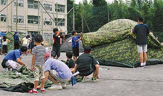 校庭にテントを張る児童ら