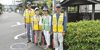 通学路に立ち安全を見守る神谷会長(右)と自治会のメンバー