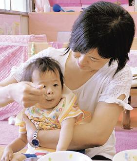 離乳食を頬張る乳児