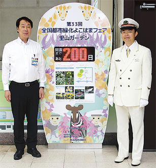 ボードを前に笑顔の名取区長(左)と中山駅長