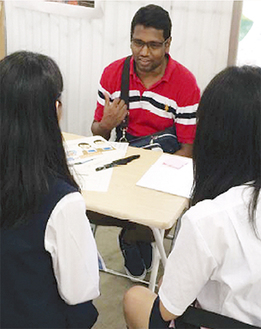 インド人男性と英語で話し合う生徒ら