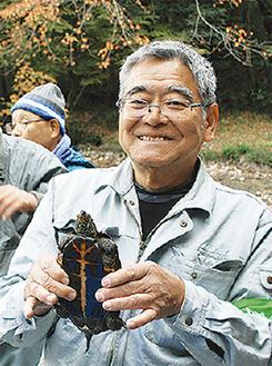 捕獲したカメを持つ町田会長