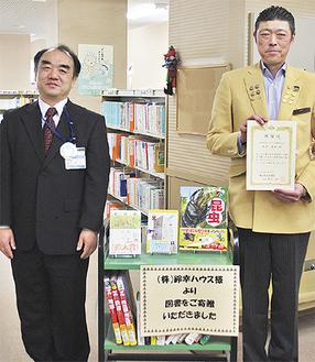 寄贈本を前に笑顔の渡辺館長(左)と鈴木代表
