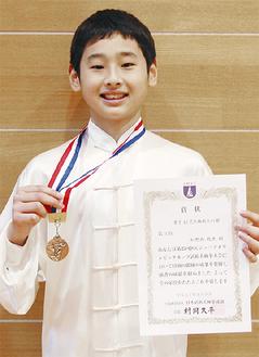 銅メダルと賞状を手に笑顔の松野内君