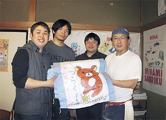 土のうを佐々木さん(右端)に手渡す塾スタッフ