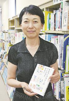 磯井さんの著書を手にする小木曽さん