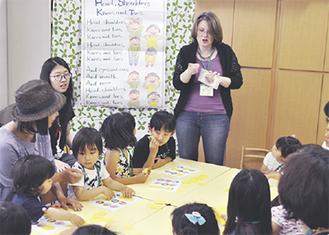 ホリーさん(中央)と英語で遊ぶ子どもたち