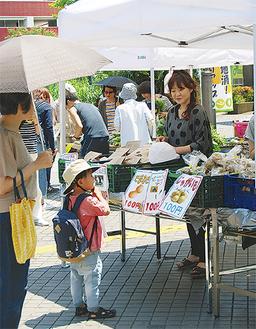 野菜販売に足を止める通行人