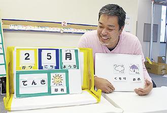 教材を手に笑顔の橋本さん