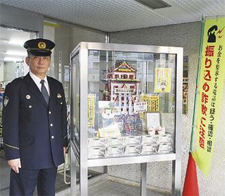 設置された「振り込ません城」の横で、被害防止を訴える竹田副署長