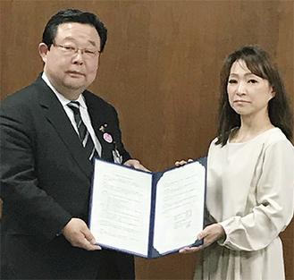 協定締結式に臨んだ田中博章こども青少年局局長(左)と江成代表